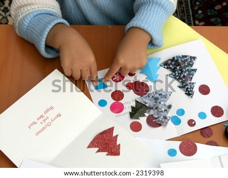A little girl learning how to make Christmas / New Year card