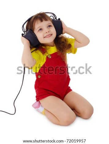 A little girl listens to music on a white background - stock photo