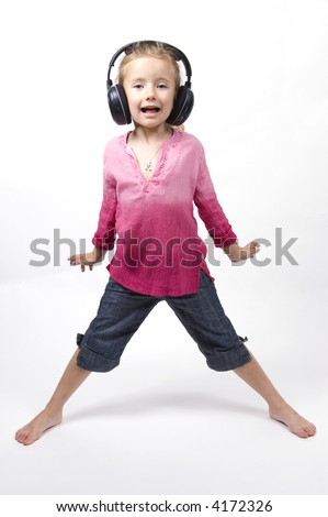 A little girl listens to music through a pair of wireless headphones - stock photo