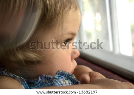 A little girl looking out a window with a tear running down her face - stock photo