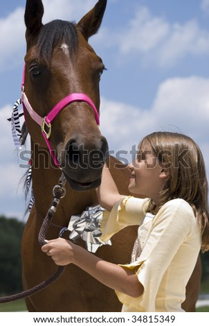 A little girl looking with joy and affection at a beautiful horse that has been given to  her as a gift on her birthday. - stock photo