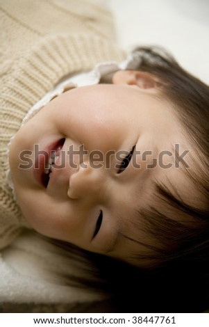 A little girl lying down is smiling.