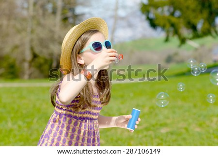 a little girl making soap bubbles with sunglasses in nature - stock photo