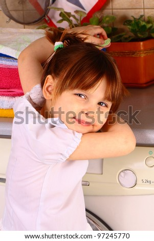 A little girl near the washing machine - stock photo