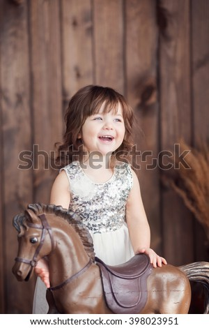 a little girl of three years standing on the floor next to a rocking horse, a beautiful light, sun, happy child, smiling with teeth - stock photo