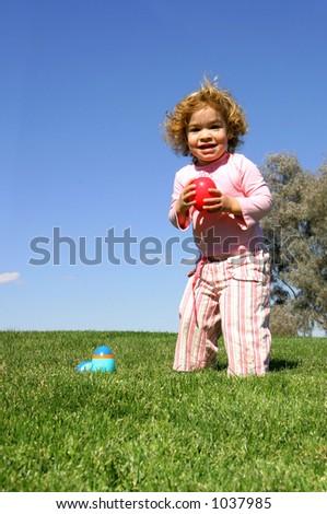 A little girl on an Easter Egg hunt. - stock photo