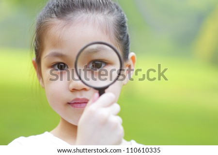 A little girl peers at the camera through a magnifying glass. - stock photo