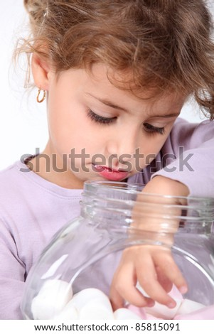 A little girl picking a marshmallow. - stock photo