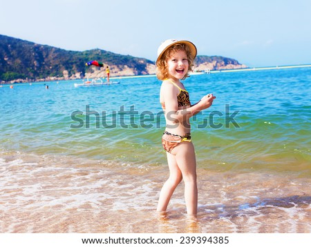 A little girl playing at the beach - stock photo
