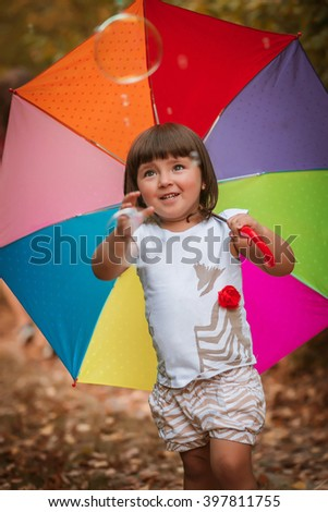 A little girl playing in the park with soap bubbles in summer. A child holding an umbrella walks in the woods on a sunny autumn day. Children playing outdoors.