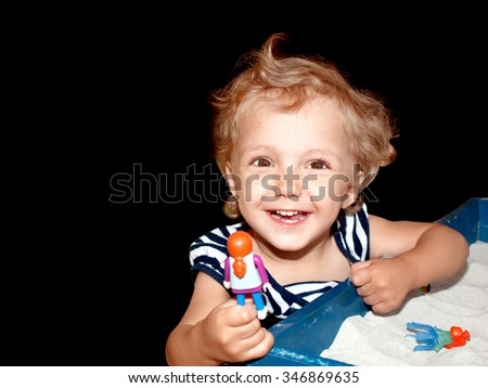 A little girl playing in the sand toys isolated black background - stock photo