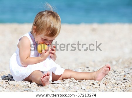 A little girl playing on the beach in summer - stock photo