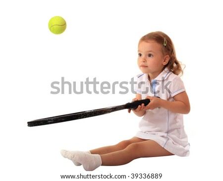 A little girl plays tennis. - stock photo