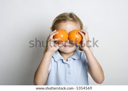 A little girl plays with 2 oranges - stock photo