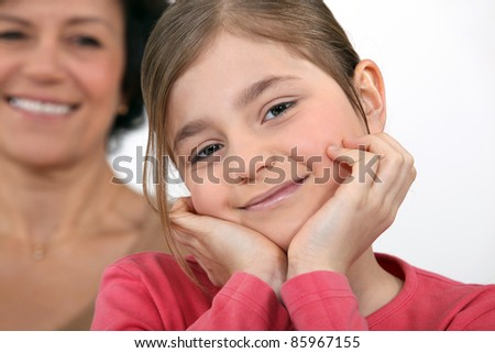 A little girl posing with her mother in the background. - stock photo