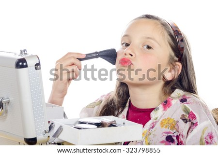 a little girl puts makeup of his mother on white background - stock photo