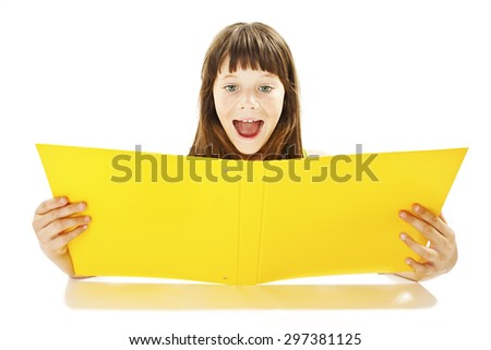 A little girl reading a big yellow book. Isolated on white background  - stock photo