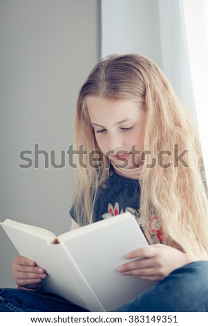 a little girl reading a book