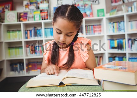 A little girl reading a book in the library