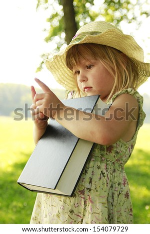 a little girl reading the Bible in nature