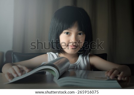A little girl reading the book - stock photo