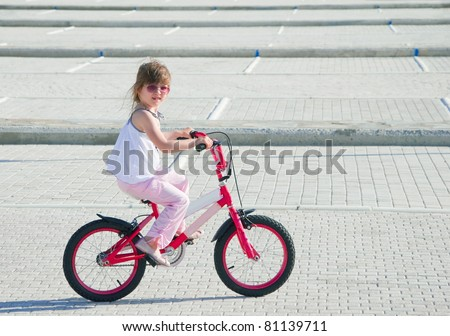 A little girl riding her bicycle - stock photo