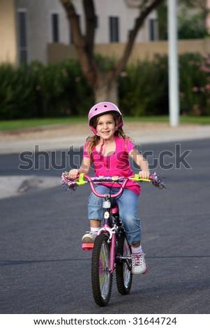 A little girl riding her bike in the neighborhood. - stock photo