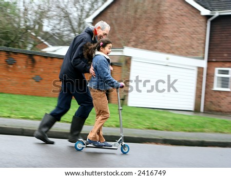 A little girl riding on her inline scooter pushed gently by her grandfather, showing lots of movement. - stock photo