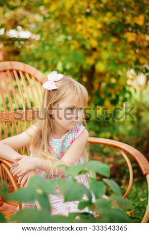 a little girl sits on a chair outdoors
