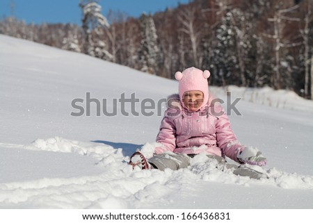 A little girl sits playing in the snow on the background of the forest