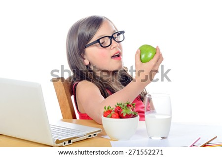 a little girl sitting at his desk eating an apple on white - stock photo