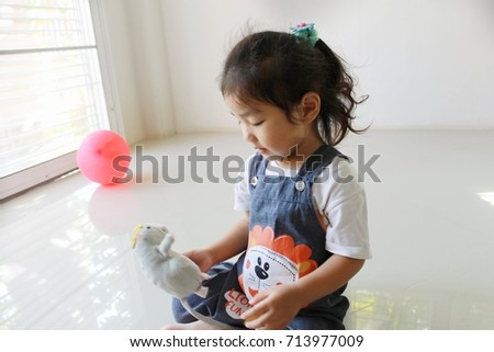 A little girl sitting at home playing a doll,little girl wear bib set