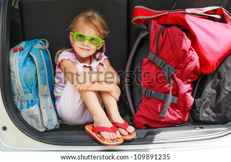a little girl sitting in the car with backpacks - stock photo