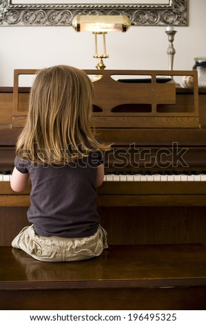 A little girl sitting on a bench and playing the piano. - stock photo