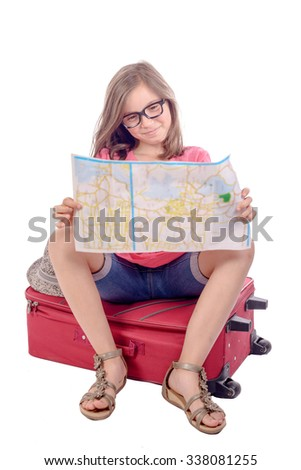 a little girl sitting on a suitcase and reading a map on white background