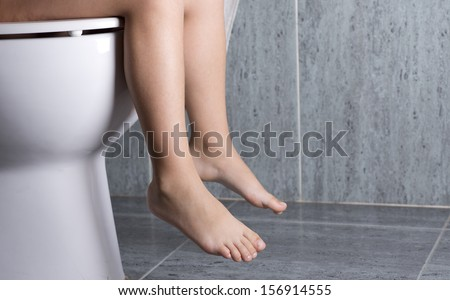 a little girl sitting on a toilet peeing - stock photo