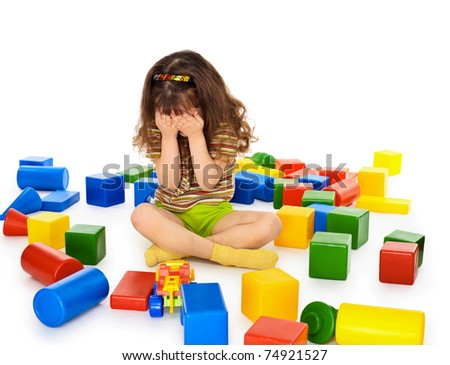 A little girl sitting on a white background among the toys and crying - stock photo