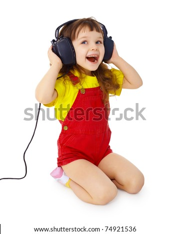 A little girl sitting on a white background with large earpieces - stock photo