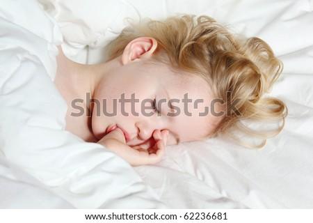a little girl sleeping, thumb-sucking and having sweet dreams - stock photo