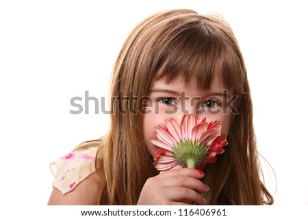 a little girl smelling a pink flower - stock photo
