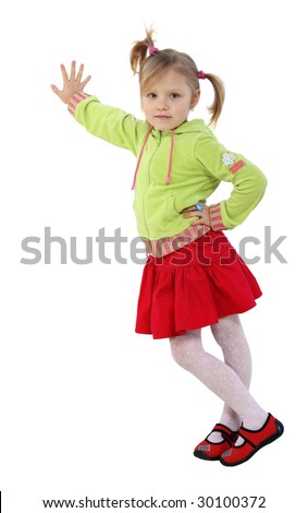 A little girl stands near a wall, red skirt, green woman's jacket, white background,  pigtails - stock photo