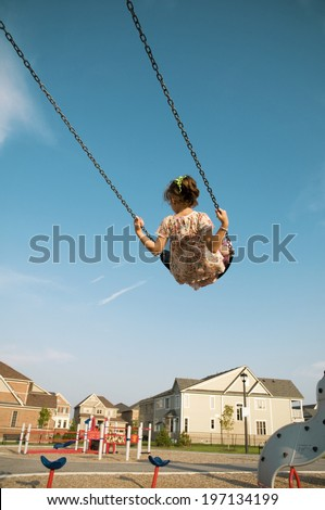 A little girl swinging high on a swing at the playground. - stock photo