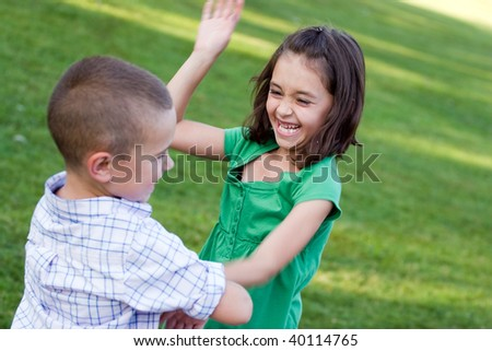 A little girl swings her arms at her brother as they rough house playfully.  Slight motion blur on the arms. - stock photo