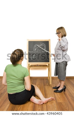 A little girl teaching a grownup of the way that a child thinks: the image on the blackboard is not a hat, that is an elephant inside a snake. - stock photo