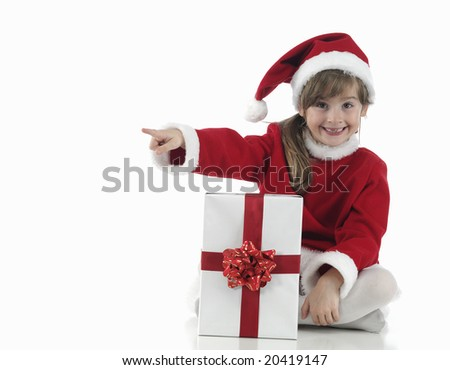A little girl that indicates and xmas presents on white background - stock photo