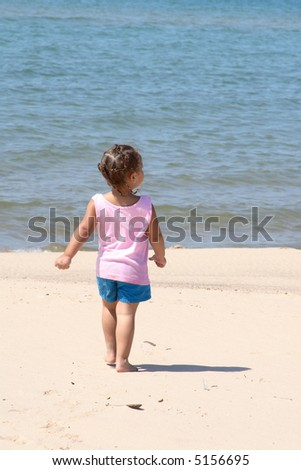A Little girl walking alone on the beach