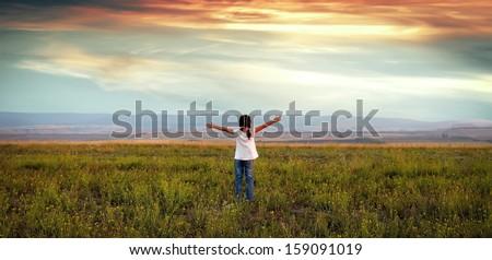 A little girl walks through the beautiful meadow - stock photo