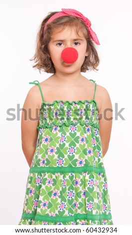 A little girl wearing a red clown nose - stock photo