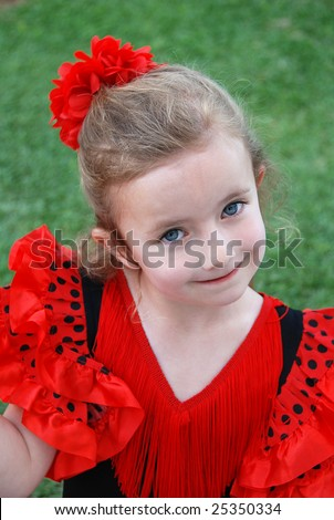 A little girl wearing a traditional flamenco costume - stock photo