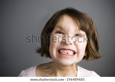 A little girl with a big grin showing off her missing tooth. - stock photo